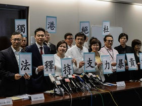 Pro-Beijing legislators including Priscilla Leung (front 3rd L) hold up placards in support of a ruling by Beijing on two elected pro-independence lawmakers from the city's legislature, at the start of a press conference in Hong Kong on November 7, 2016.