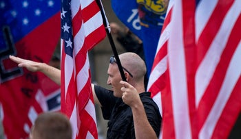 An illustrative photo shows a member of a white supremacy group giving the fascist salute during a gathering in West Allis, Wisconsin.