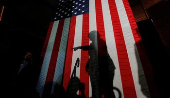 U.S. Democratic presidential nominee Hillary Clinton casts a shadow on a U.S. flag at the conclusion of a campaign rally in Manchester, New Hampshire, U.S. November 6, 2016.