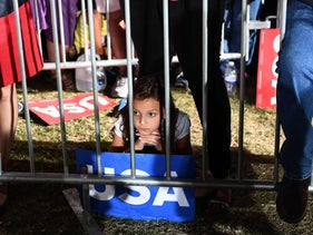 A young girl listens to U.S. Democratic presidential nominee Hillary Clinton during a campaign rally in Tempe, Arizona, on November 2, 2016.