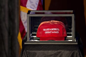 """A """"Make America Great Again"""" hat sits in a case on the stage in the grand ballroom of the Hilton Midtown hotel ahead of Donald J. Trump, 2016 Republican presidential nominee's election night event in New York, U.S., on Tuesday, Nov. 8, 2016."""