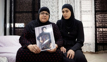 In this photo taken Thursday, Nov. 3, 2016. Israeli Arab Majeda Abu Sharkh left, holds a picture of Duaa Abu Sharkh that was killed in Lod as she poses for a photograph with her niece Alaa Khalili, in Lod, central Israel.