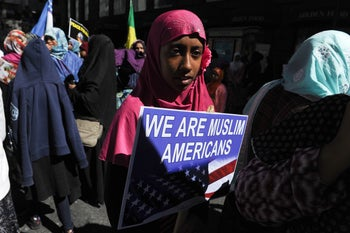 A girl wearing a Muslim headscarf holds a sign during the annual Muslim Day Parade in the Manhattan borough of New York City, September 25, 2016.