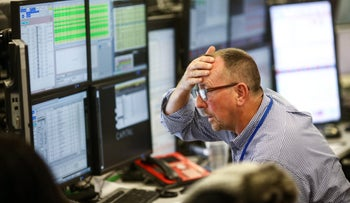 A trader reacts as he looks at financial data on computer screens on the trading floor at ETX Capital, a broker of contracts-for-difference in London, U.K., on Wednesday, Nov. 9, 2016.
