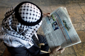 A Palestinian man reads the Al-Quds newspaper depicting images newly elected U.S. President Donald Trump and Democratic presidential nominee Hillary Clinton in Jerusalem's Old City November 9, 2016.