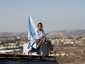 A boy sits near an Israeli flag atop the roof of a vehicle at the entrance to the settler outpost of Amona in the West Bank, October 20, 2016.