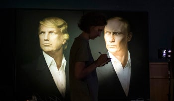 A journalist standing on a backdrop of portraits of Donald Trump and Vladimir Putin in the Union Jack pub in Moscow, Russia,  Nov. 9, 2016.