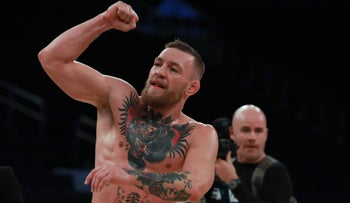 UFC Featherweight Champion Conor McGregor takes part in UFC 205 Open Workouts at Madison Square Garden on November 9, 2016 in New York City. McGregor, bearded, bare-chested and heavily tattooed,pumps a fist in the air.