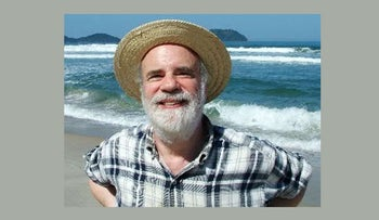 Saul Kripke, smiling widely and featured wearing a straw hat. His hair seems to be silver-white, though most is covered by the hat. His mustache and bears are almost entirely white. He is standing on Juquehy Beach, Sao Paolo, and is wearing a sort of plaid button-up shirt. Picture date:  1 August 2005.