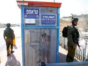 Israeli soldiers stand next to a bus stop with Donald Trump posters, near the West Bank city of Ariel, October 6, 2016.