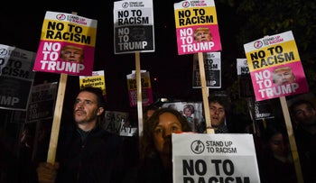 Demonstrators hold placards at a protest against President-elect Donald Trump outside the U.S. Embassy in London, November 9, 2016.