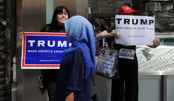 A woman wearing a Muslim headscarf walks past Donald Trump supporters in New York, September 25, 2016.