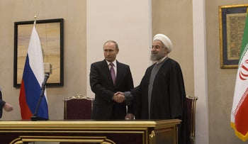 Vladimir Putin, Russia's president, left, and Hassan Rouhani, Iran's president, shake hands after a press conference at the Gas Exporting Countries Forum (GECF) summit in Tehran, Iran, on Monday, Nov. 23, 2015.