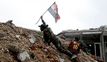 A Syrian army solder places a Syrian national flag during a fight with rebels near Aleppo, December 5, 2016.