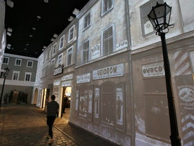 In this Friday, Oct. 10, 2014 photo, a visitor walks through a gallery depicting a street scene typical of those found between 1919 and 1939 at the POLIN Museum of the History of Polish Jews in Warsaw, Poland.