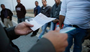 Border Policeman checking IDs and work permits of Palestinian workers.