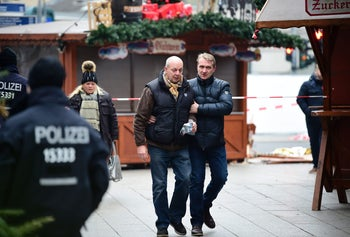 A market salesman is comforted as he arrives at the Christmas market the day after the deadly truck ramming, Berlin, Germany, December 20, 2016.