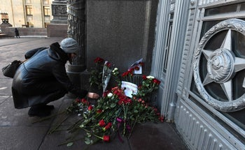 A woman lays a flower outside the Russian Foreign Ministry in Moscow following the assassination of Russia's ambassador to Turkey on December 20, 2016.