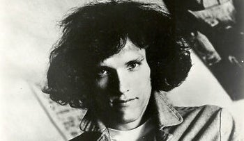 Jorma Kaukonen with Jefferson Airplane; shown with fairly long hair, passing his ears, a light-colored T-shirt and holding the lapels of his jacket.