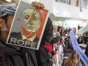 A man holds up a poster designed by a Bezalel student during a protest against censorship held at the Jerusalem art school on December 15, 2016.
