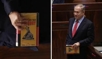"""Netanyahu at the Knesset on Dec. 21, 2016 holding """"Nothing Less than Victory"""" by John David Lewis."""