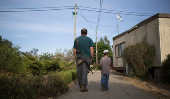 A Jewish settler walks with his son in the Jewish settlement of Maon, south of Hebron, in 2014.