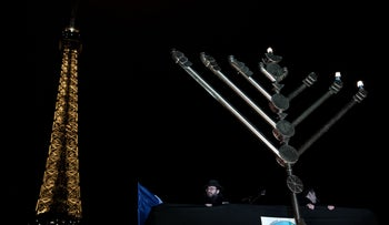 A member of the Jewish community stands under a hanukkia in front of the Eiffel tower in Paris on December 25, 2016.