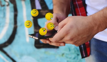 Emojis hover above a smartphone held by a man.