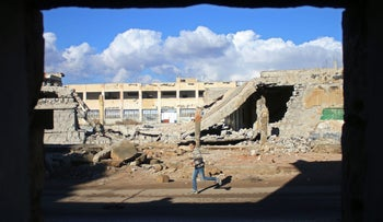 A Syrian boy runs past the rubble of destroyed buildings in the rebel-held area of Daraa, in southern Syria, on January 1, 2017.