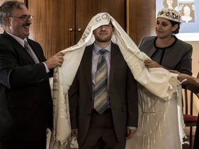 Arie Hasit, center, is ordained a rabbi at the Schechter Rabbinical Seminary in Jerusalem, Sept, 14, 2016. Hasit is covered by tallit, surrounded by a man and two women.