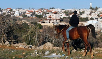 A picture taken from Hebron shows a Palestinian boy riding a horse, with the Israeli settlement of Givat Harsina appearing in the background, West Bank, February 5, 2017.