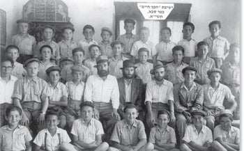 Rabbi Aharon Leib Shteinman (in the center with a suit and hat) with his students at the Chafetz Chaim Yeshiva in Kfar Sava, 1951.