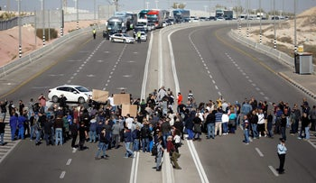 Workers of Teva Pharmaceutical Industries block a road during a demonstration near the facility in Neot Hovav, southern Israel