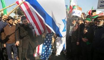 Iranian demonstrators burn representations of U.S. and Israeli flags in a pro-government rally in the northeastern city of Mashhad, Iran, Jan. 4, 2018.