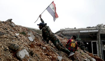 A Syrian army soldier places a Syrian national flag during a battle with rebel fighters at the Ramouseh front line, east of Aleppo, Syria on Monday, December 5, 2016