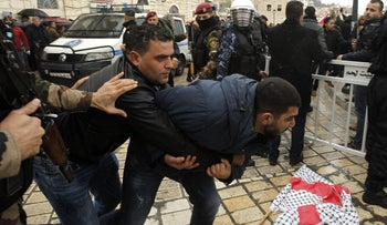 Palestinian policemen scuffle with protesters in Bethlehem on January 6, 2018