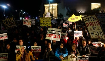 """Anti-corruption protesters hold signs reading, """"Corrupt ones, go home,"""" at a rally in Tel Aviv, January 6, 2018"""