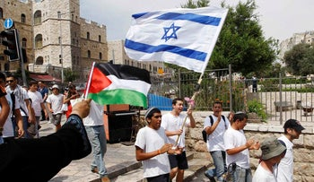 Woman waves Palestinian flag as Israeli youths with Israeli flag walk by in Jerusalem