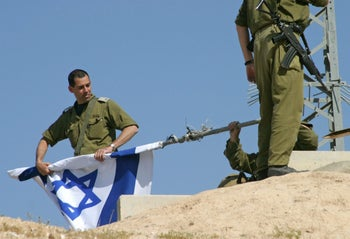 An Israeli soldier rolls an Israeli flag after the dismantling of an Israeli army checkpoint in the West Bank city of Jericho March 16, 2005