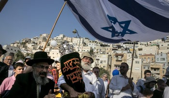 Matityahu Dan, chairman of the Ateret Cohanim organization, holds a Torah scroll as part of a Jewish procession in Silwan in East Jerusalem last year
