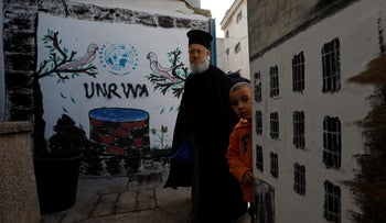 A Palestinian man walks past a logo of United Nations Relief and Works Agency (UNRWA) in Jalazone refugee camp, near the West Bank city of Ramallah January 3, 2018.