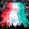 Pro-government demonstrators parade an oversized Iranian flag during a march in Iran's holy city of Qom. January 3, 2018