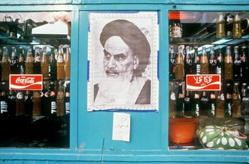 A poster of Ayatollah Ruhollah Khomeini displayed in a shop window next to bottles of Coca-Cola, in Tehran.  January 1, 1979