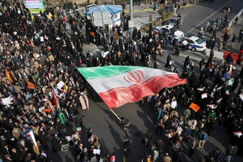 A demonstrator waving a huge Iranian flag during a pro-government rally in the northeastern city of Mashhad, Iran, January 4, 2018.