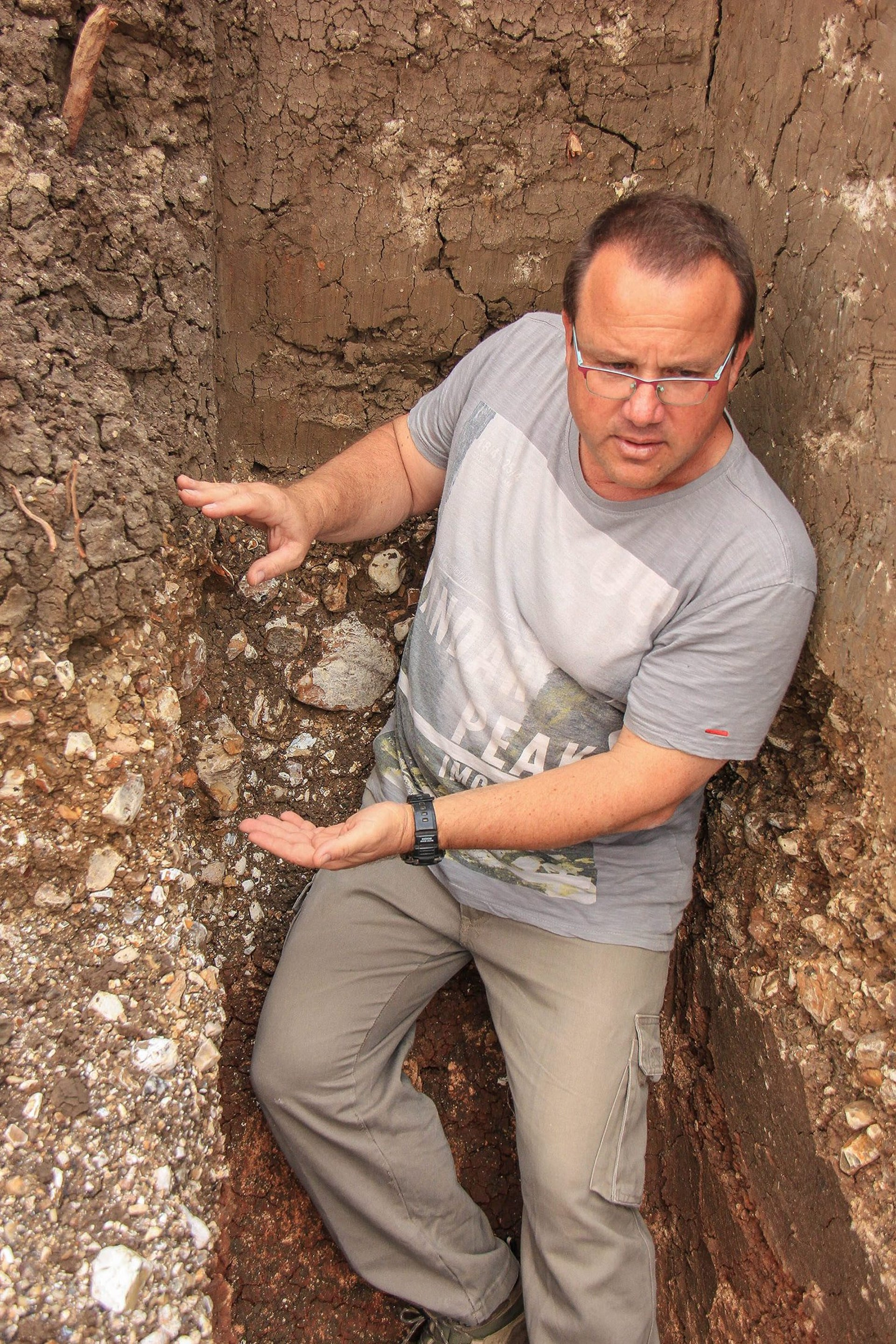 Tel Aviv University archaeologist Ran Barkai shows a sections of sediments filled with pieces of flint and tools at a prehistoric site in Jaljulia.