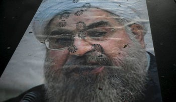 A picture shows a  portrait of Iranian President Hassan Rouhani with shoe marks over it during a demonstration in support of the Iranian people amid a wave of protests spreading throughout Iran, on January 3, 2018