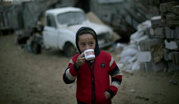 A Palestinian boy drinks tea outside his family's house on the outskirts of the Khan Yunis refugee camp, Gaza, January 5, 2018.