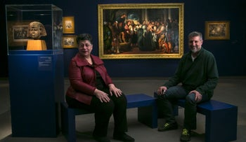 The head of the museum's restoration lab Ghiora Elon and the curator of the exhibition Shlomit Steinberg sitting next to the painting.