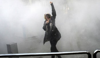 In this Dec. 30, 2017 photo made by an individual not employed by the Associated Press and obtained by the AP outside Iran, a university student attends a protest inside Tehran University while a smoke grenade is thrown by Iranian police, in Tehran, Iran