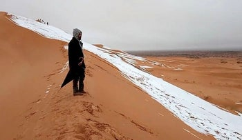 A man looks at at a snow-covered slope in the Sahara, Ain Sefra, Algeria, January 7, 2018 in this picture obtained from social media